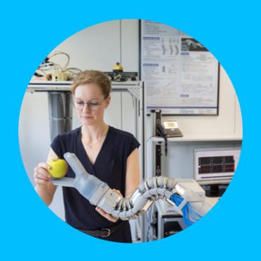 Eine Studentin legt einen Apfel in den Greifarm eines Kontinuum-Roboterarms. Eine Studentin legt einen Apfel in den Greifarm eines Kontinuum-Roboterarms.