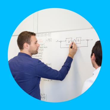 Ein Student zeichnet einen Regelkreis an eine Tafel. Ein Student zeichnet einen Regelkreis an eine Tafel.