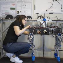 Eine Studentin arbeitet an einem vierbeinigen Roboter.