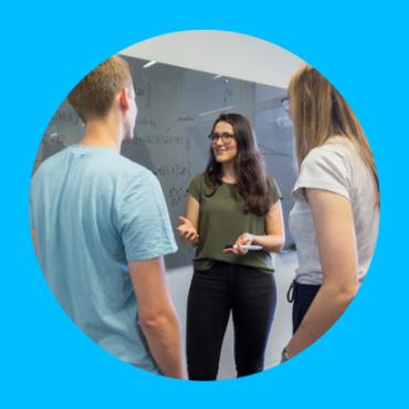 Eine Studentin erklärt anderen eine mathematisches Konzept vor einer Tafel. Eine Studentin erklärt anderen eine mathematisches Konzept vor einer Tafel.