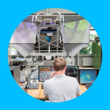 Ein Student schaut sich Bildschirme vor einem hydraulischen Flugsimulator an. Ein Student schaut sich Bildschirme vor einem hydraulischen Flugsimulator an.